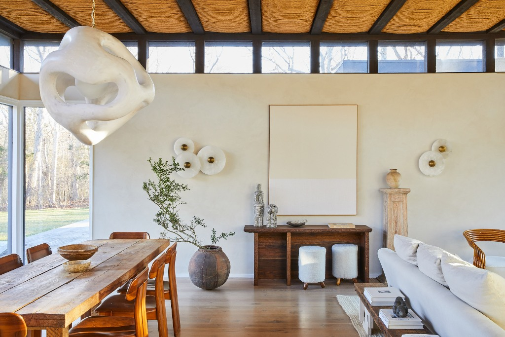 The living room and dining spaces are united in one, glazed walls and skylights fill the layout with natural light