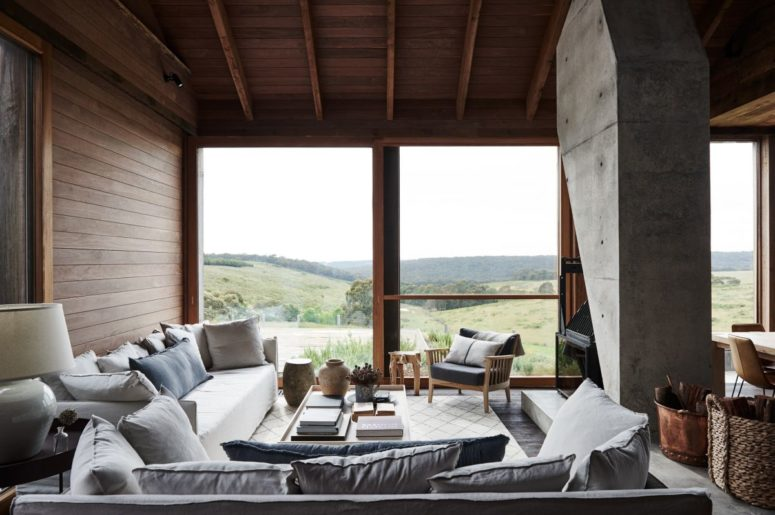 The living room features a glazed wall, wooden furniture and comfy sofas around a hearth cast in concrete