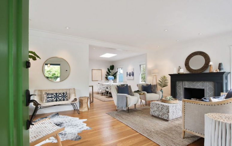 The living room is neutral, with chic mid-century modern furniture, a tile clad fireplace and several rugs