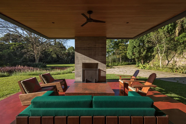 The terrace features a fireplace, a stone table, some comfortable furniture in modern style