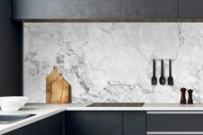 03 a black minimalist kitchen with sleek cabinets, neutral stoen countertops and a white marble backsplash