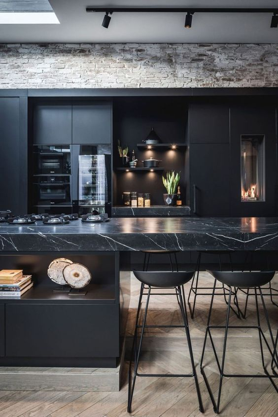a black moody kitchen with plain cabinets and a stunning black marble kitchen island for a refined feel