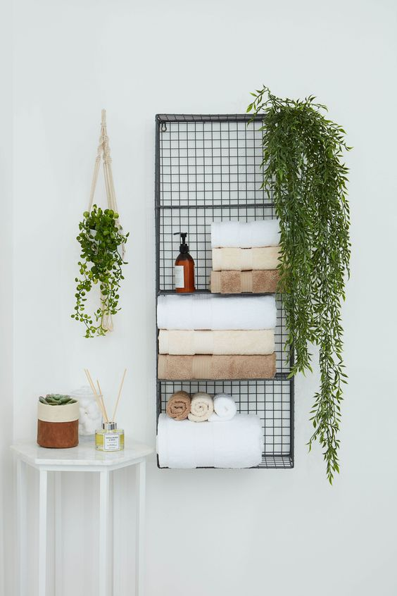 a metal wall shelf for storing towels, soaps, greenery in pots is a nice solution to save some floor space