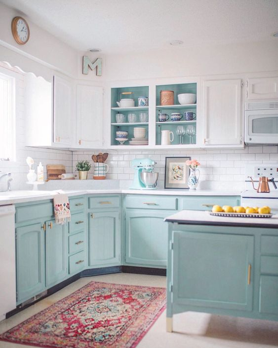 a two-tone kitchen with white uppers and light blue lowers plus gold hardware looks cool