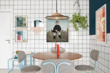 The dining space is clad with white square tiles, there are cool grey chairs and a catchy gallery wall plus a blush pendant lamp