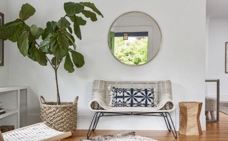 The entryway is styled with a cool curved bench and some woven and wooden items