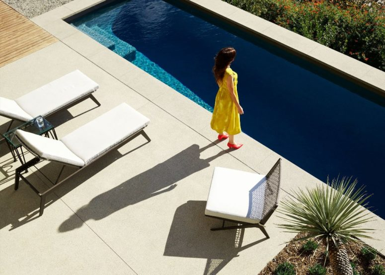 There's a long and narrow pool and white loungers and chairs by its side