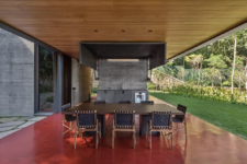 04 There's an outdoor kitchen done with metal and stone, and a dining space with a wooden table and leather chairs