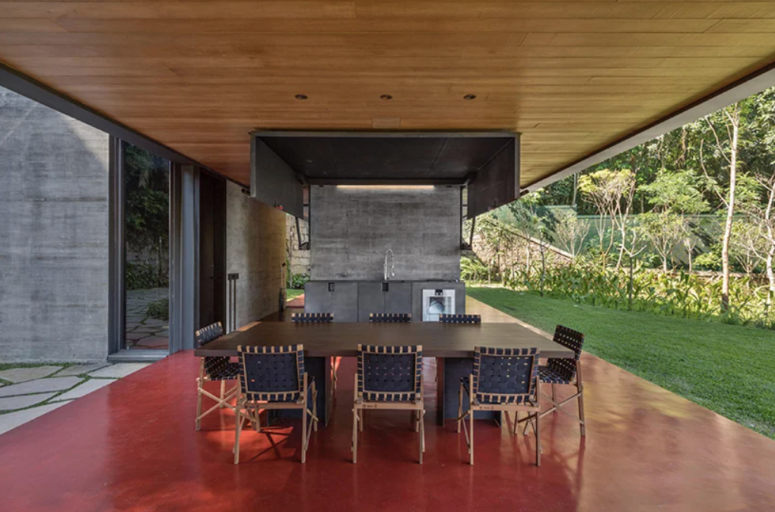 There's an outdoor kitchen done with metal and stone, and a dining space with a wooden table and leather chairs