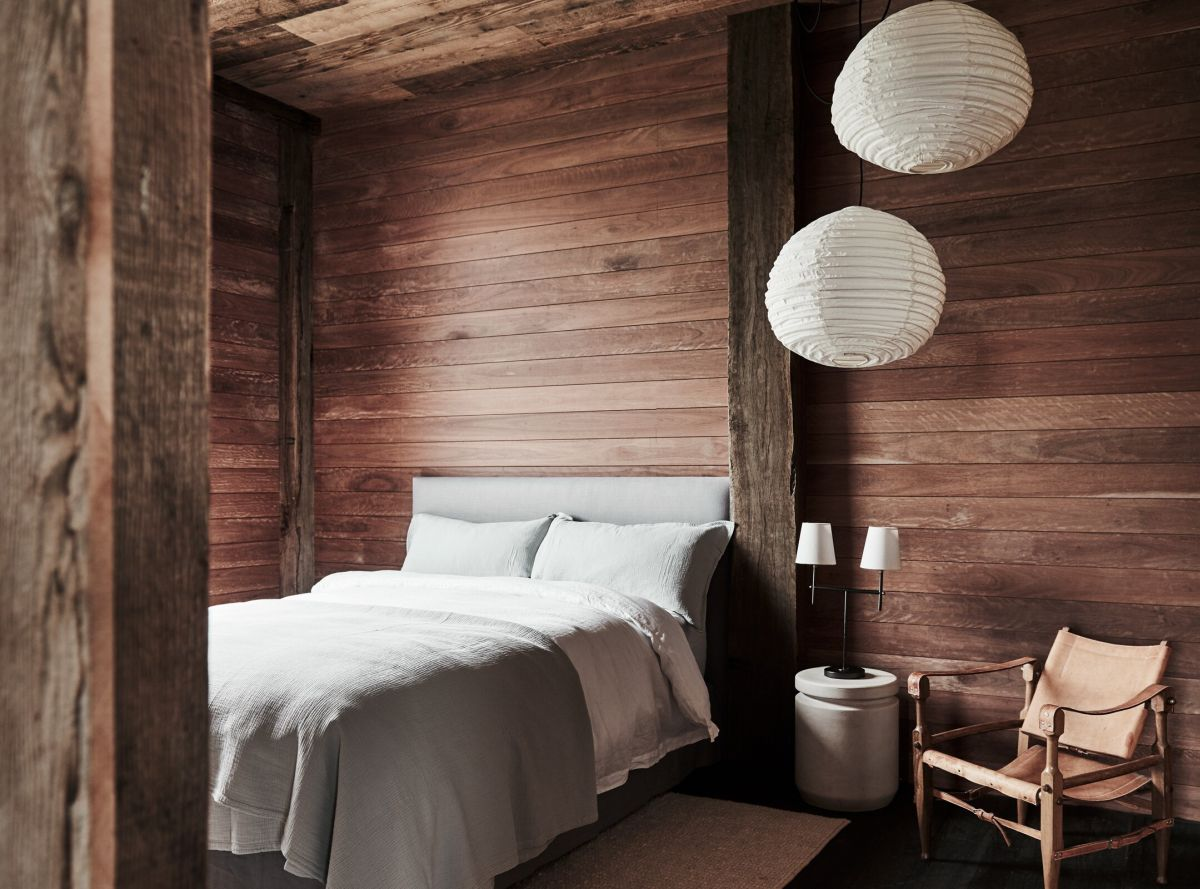This bedroom is fully clad with wood, there's a comfy bed, some paper lamps and a leather chair