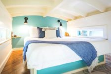 04 Upstairs there's a bedroom with small windows, an accent turquoise wall and a large comfy bed