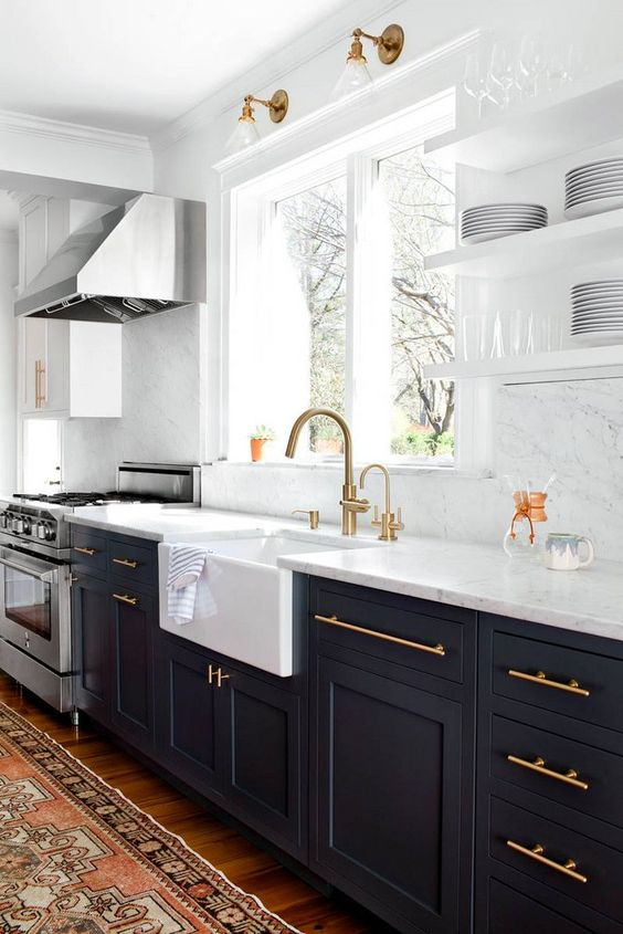 a black kitchen with white stone countertops and a backsplash looks very contrasting
