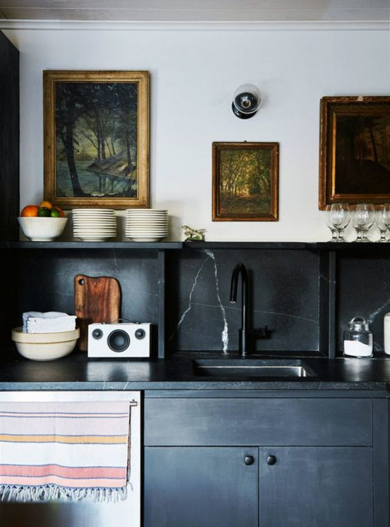a black vintage inspired kitchen with a black marble backsplash and countertops for a refined touch