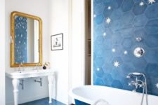 04 a bright bathroom clad with blue hexagon tiles and with stars printed on them, blue and white bathtub and a white free-standing sink