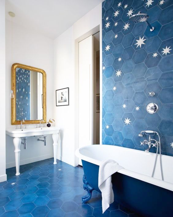 a bright bathroom clad with blue hexagon tiles and with stars printed on them, blue and white bathtub and a white free-standing sink