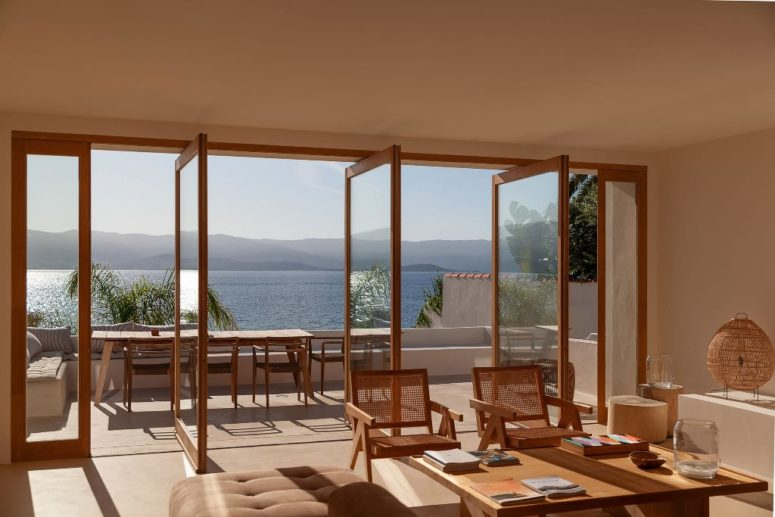 Several pivot glass doors open the indoor space to a terrace with a dining space