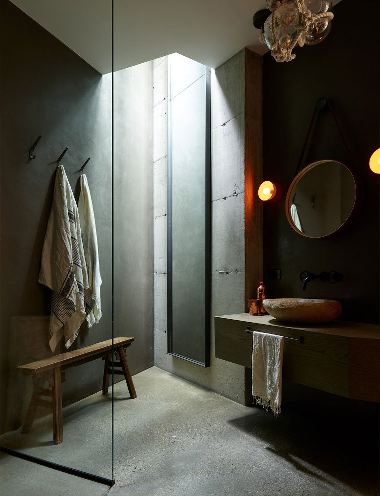 The bathroom features concrete walls and a floor, a stone tub and a floating vanity