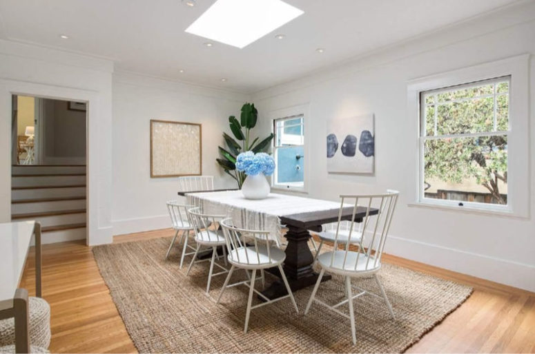 The dining space is done with a dark stained dining table, a skylight and some matching chairs