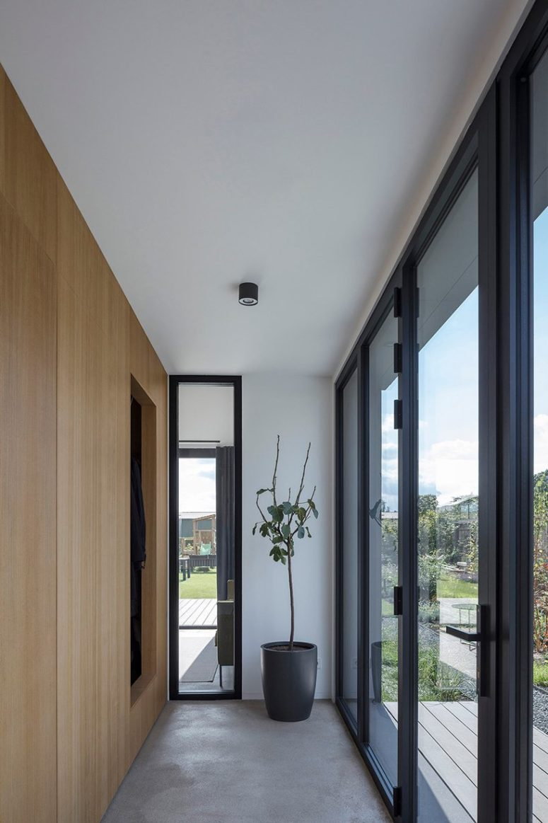 The entryway is minimal, there's a large sleek storage unit and a statement plant in a pot