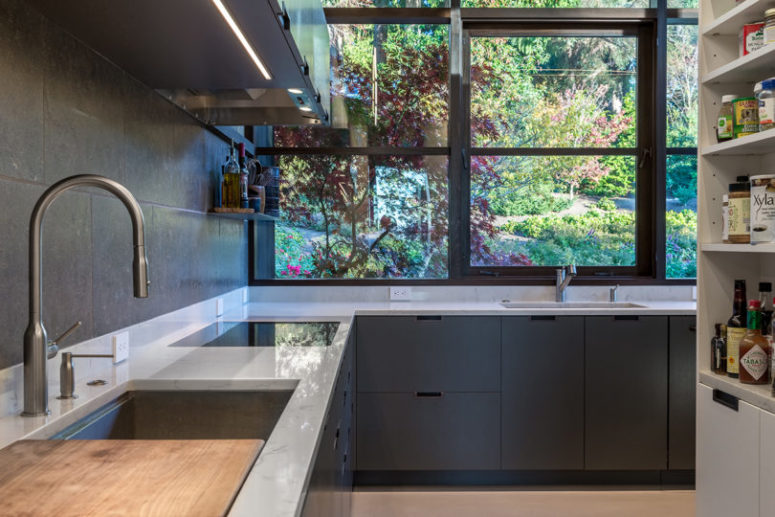 The kitchen is done with sleek graphite grey cabinets, white stone countertops and a glazed wall instead of a backsplash