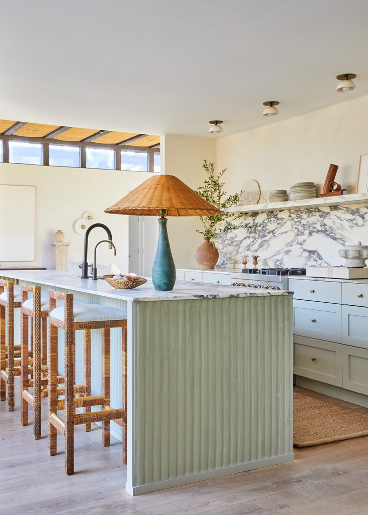 The kitchen is mint green, the countertops and a backsplash are of white marble, and you can see some wicker items here
