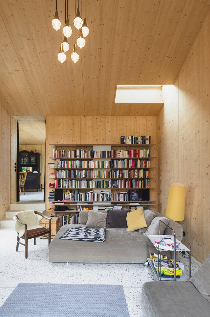 The living room is clad with light-colored wood, there are skylights and a wall of books