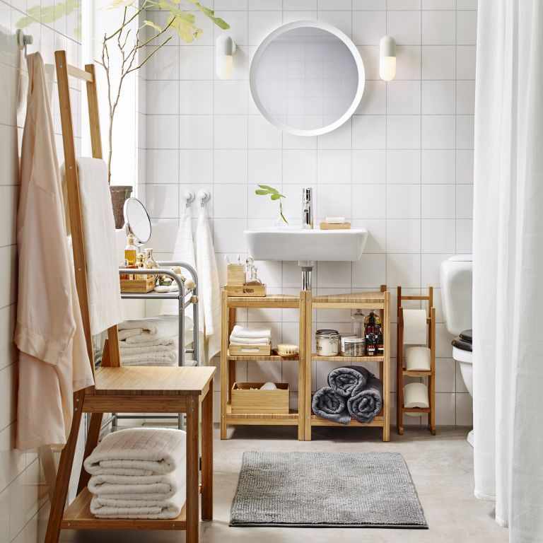 a chic contemporary bathroom done in neutrals and with simple furniture, with towels in the vanity and inside a stool