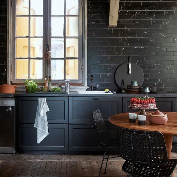 a chic moody kitchen with black marble tiles cladding a whole wall for a refined and bold touch