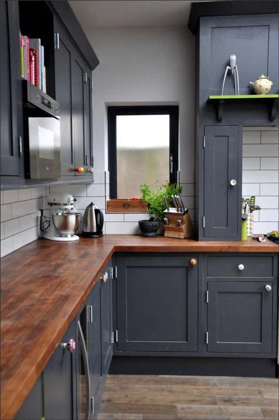 a graphite grey kitchen with rich tone wooden countertops and a white tile backsplash
