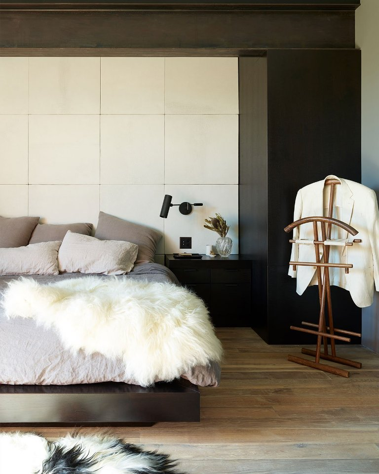 The bedroom shows off a contrasting color schemes, a luxurious bed and sconces