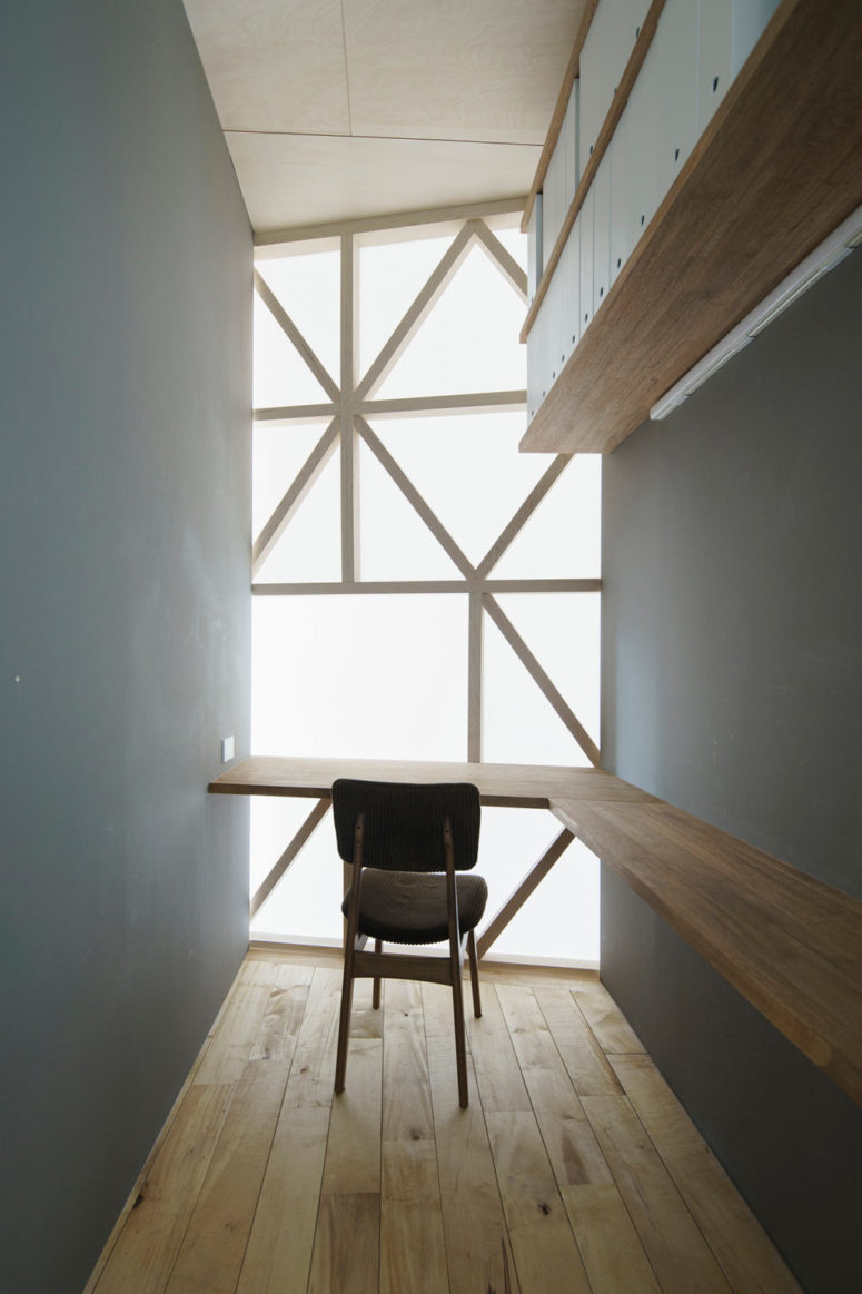 The home office is tiny, it features a floating desk, open shelves and natural light coming through the curtain
