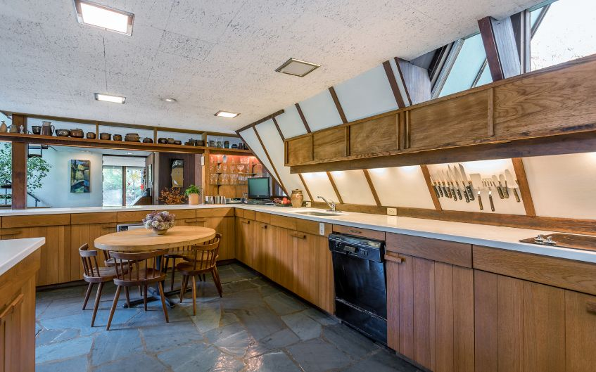 The kitchen is clad with wood and white stone, there are several windows and skylights