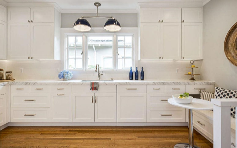 The kitchen is white, with a stone countertop and a small and cozy breakfast nook with a built-in seat