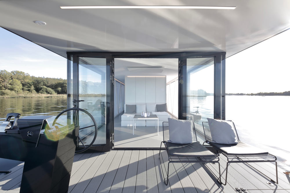 The lower terrace or deck features a couple of loungers and glass doors to inside