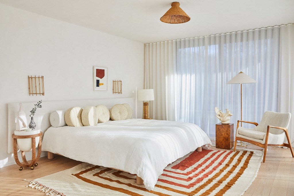 The master bedroom is mid century modern, mostly neutral but with a striped rug and touches of wicker and stone