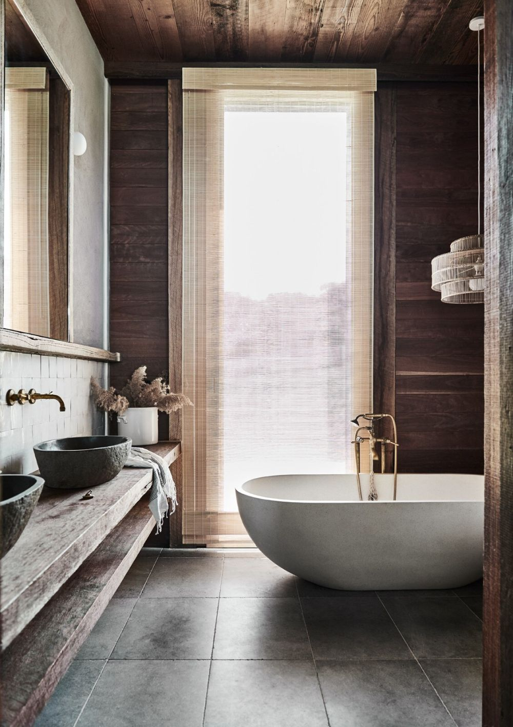 This bathroom features much natural wood, tiles, a white stone tub and even some views