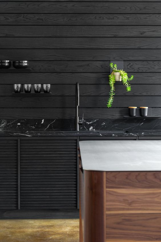 a moody kitchen with black plank walls, a black marble countertop and a wooden kitchen island with a white stone countertop