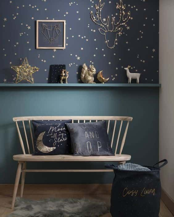 a romantic nook with navy and gold star wallpaper, some stars and moon figurines and matching pillows