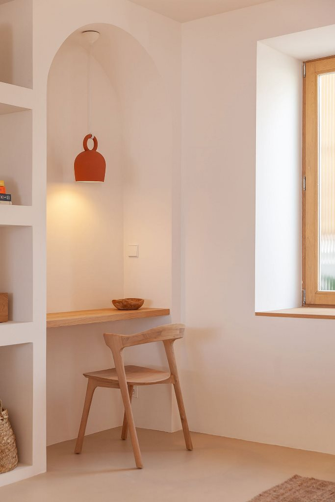 A small home office nook shows off a tiny desk and a wooden desk