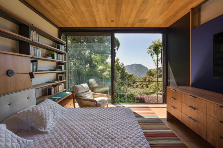 The bedroom features a glazed wall, a shelving unit on one wall and a large TV