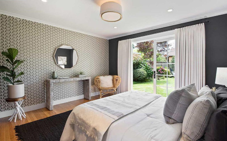 The bedroom is done with a printed wallpaper wall, a glass door to the garden and some stylish furniture