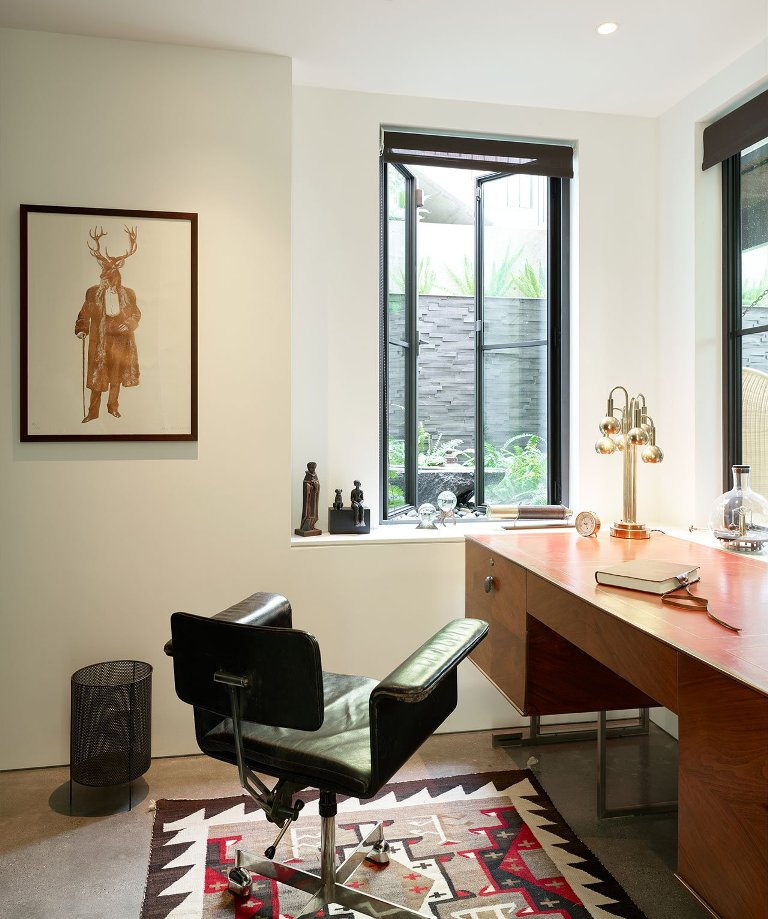 The home office is done with stylish mid-century modern furniture and much natural light