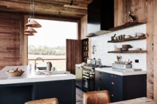 07 The kitchen is done in navy and white, with leather handles and a white tile backsplash