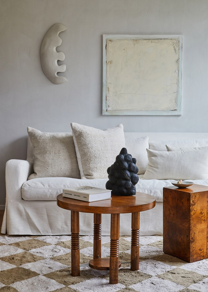 The living room is done with a white sofa, a wooden table and some simple pillows
