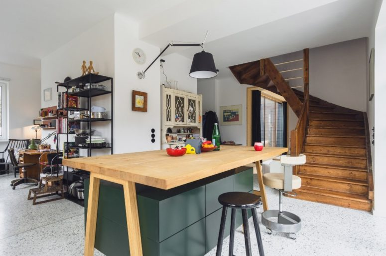 There's a large quirky kitchen island with sleek green drawers and a wooden countertop