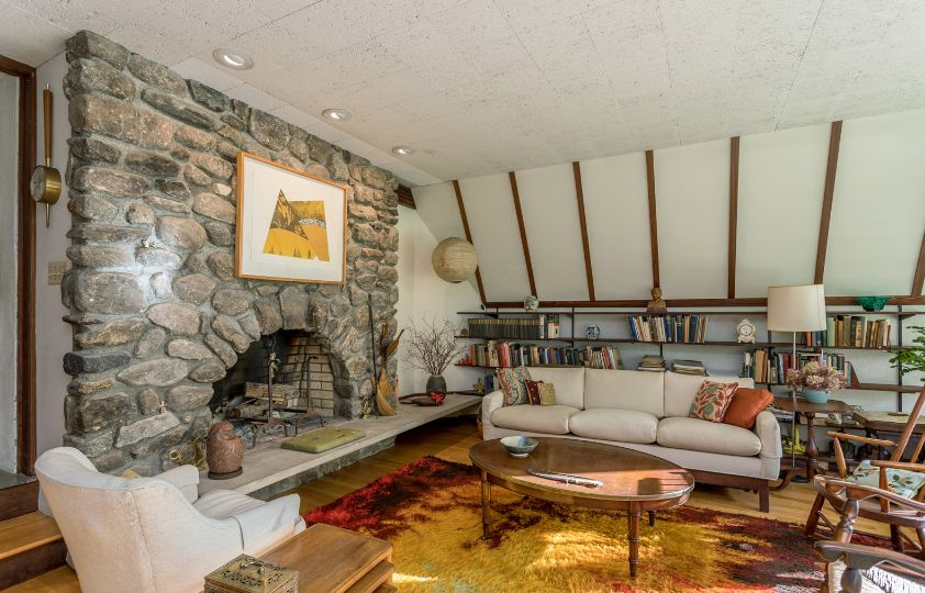 There's another living room with white walls, a stone fireplace and comfy mid century modern furniture