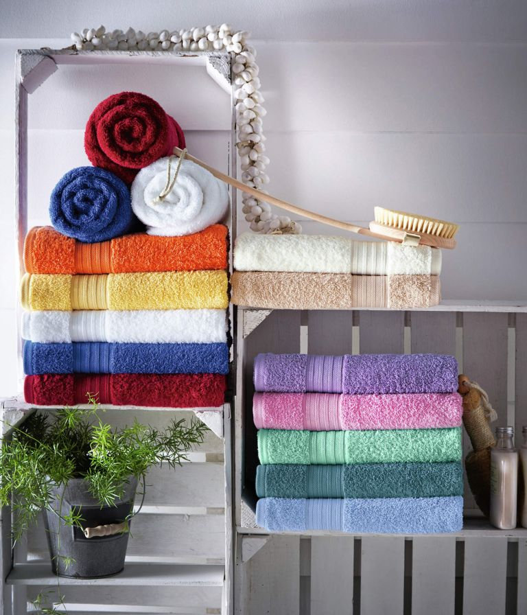 crates repurposed into wall shelves to store towels, a plant and other bathroom stuff you may need