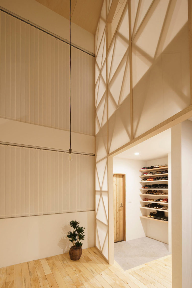The entryway is clean and minimal, with open shelves for shoes and a rug