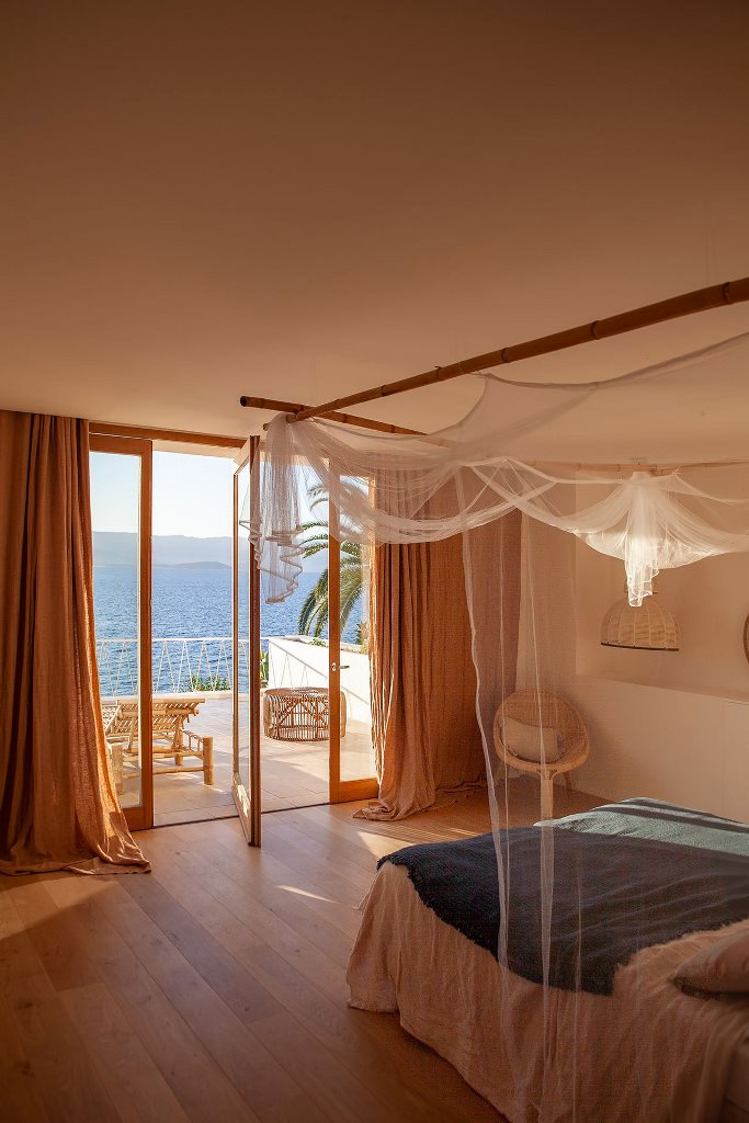 The master bedroom shows off amazing sea views and a large balcony with loungers, a bed with a canopy
