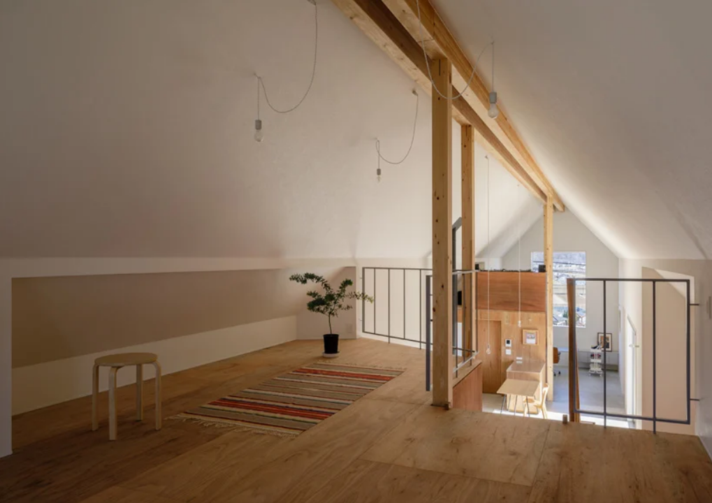 There's a loft bedroom with bulbs, a striped rug and some comfy furniture here